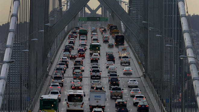 FILE - In this Dec. 10, 2015, file photo, vehicles make their way westbound on Interstate 80 across the San Francisco-Oakland Bay Bridge as seen from Treasure Island in San Francisco. California officials on Friday, Oct. 26, 2018, blasted the Trump administration's plan to freeze vehicle emissions standards, saying it threatens public health and the environment and was based on a flawed scientific analysis. (AP Photo/Ben Margot, File)
