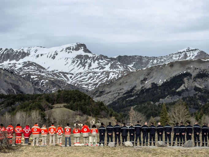 French rescue workers gather in front of a memorial