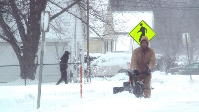 In this Tuesday, Dec. 26, 2017 photo, a man uses a snow blower to dig out after heavy snow fell in Dunkirk, N.Y.