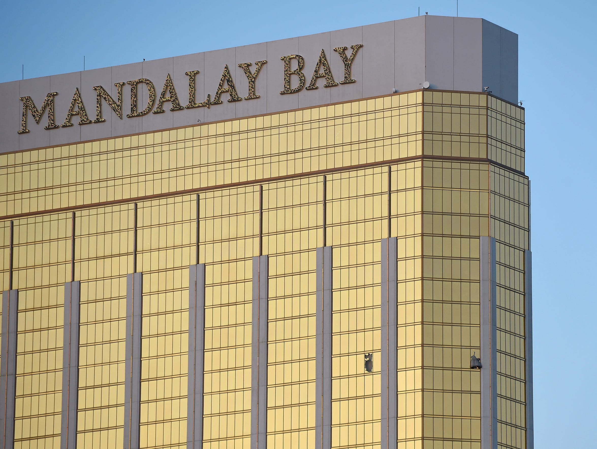 Broken windows are seen on the 32nd floor of the Mandalay