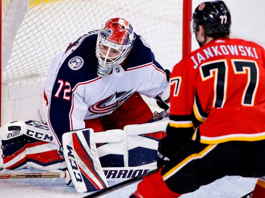 Columbus Blue Jackets goaltender Sergei Bobrovsky (72), from Russia, makes a save against Calgary Flames center Mark Jankowski (77) during the third period of an NHL hockey game Thursday, March 29, 2018, in Calgary, Alberta. (Larry MacDougal/The Canadian Press via AP)