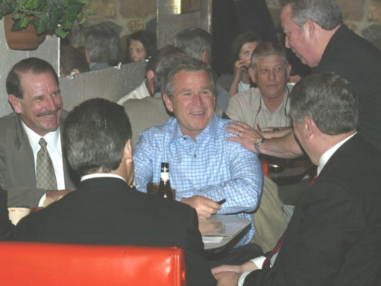 President Bush is greeted by Art Killeen, right, owner