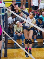 Amber Hartley (4) leaps to hit the ball over the net