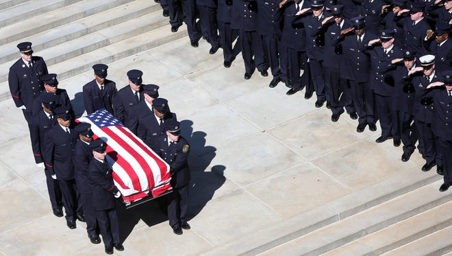 Firefighters salute as the casket carrying Gordon is carried from St. Peter in Chains Cathedral.