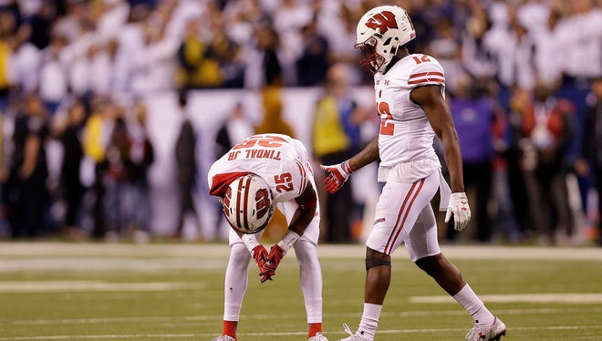 Dejected Wisconsin Badgers Derrick Tindal (left) and  Natrell Jamerson at the end of the Big Ten football championship game.
