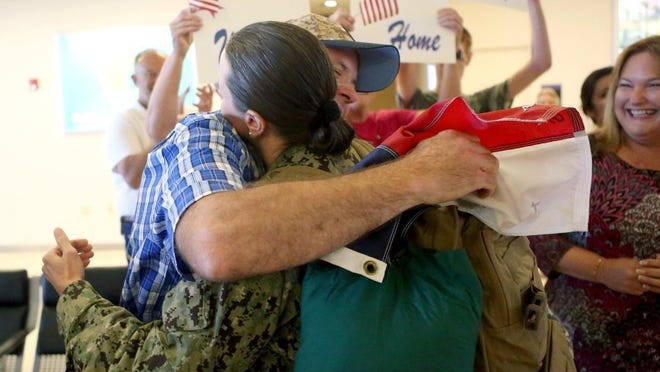 GABE HERNANDEZ/CALLER-TIMES Navy Petty Officer 1st Class Mandy Maddocks-Helman hugs her husband Dana on Wednesday at Corpus Christi International Airport. Maddocks-Helman is returning from a deployment in the Middle East.