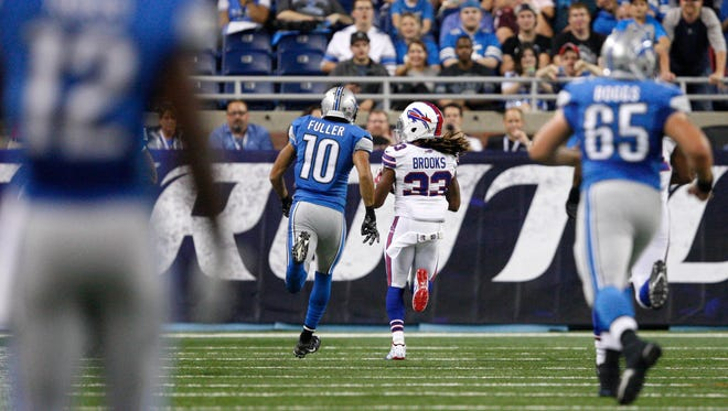 Bills cornerback Ron Brooks makes an interception for a touchdown and is chased by Detroit Lions wide receiver Corey Fuller (10) during the first quarter Thursday night.