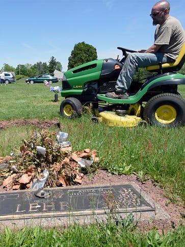 Brain Baublitz mows around a grave that needs attention