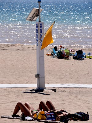 A yellow flag warns of the possibility of rip currents along Lake Michigan's First Street Beach in Manistee on June 20. Manistee no longer has lifeguards.