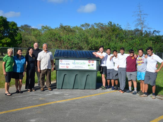i*recycle brings over a new recycling bin donated by Fokai to Father Duenas Memorial High School. Pictured from left:  Peggy Denney, i*recycle; Gloria Perez, Matson Navigation Company; Patricia Salas, Bank of Guam; Jojo Camacho, Ambros, Inc.; Mark Sablan, South Pacific Petroleum Corporation; and Steven Leung, Alvin Almira, Kai Aricayos, Aleksander Perez, Shane Calano, Orion Perez and Matthew Mariano, Father Duenas Memorial High School students.