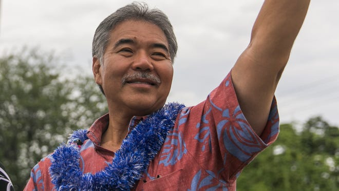 Hawaii State Sen. David Ige, right, waves to passing cars in some last minute  campaigning in the Hawaii gubernatorial primary race on Aug. 9, 2014.