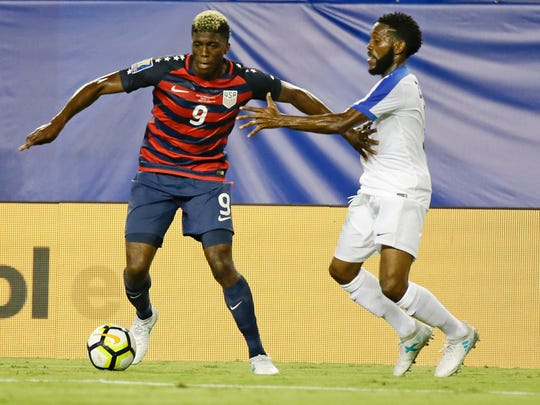 United States' Gyasi Zardes (9) makes a move towards the goal as Martinique's Nicolas Zaire tries to slow him down during a CONCACAF Gold Cup soccer match, Wednesday, July 12, 2017, in Tampa, Fla. (AP Photo/John Raoux)