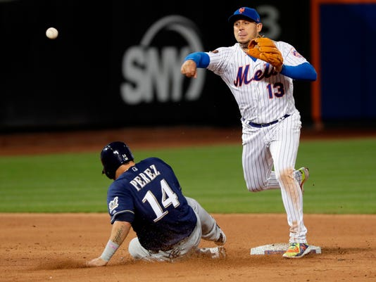 New York Mets' Asdrubal Cabrera (13) throws out Milwaukee Brewers' Orlando Arcia at first base for a double play after forcing to Hernan Perez (14) during the sixth inning of a baseball game Friday, April 13, 2018, in New York. (AP Photo/Frank Franklin II)