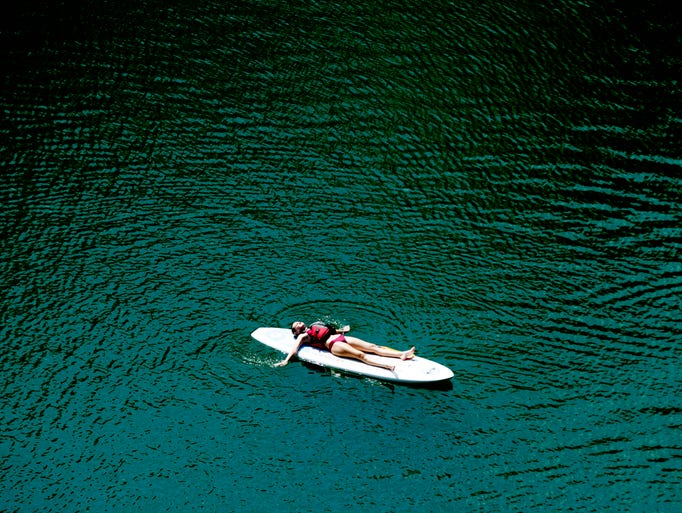 A person rests on their paddle board at Mead Quarry