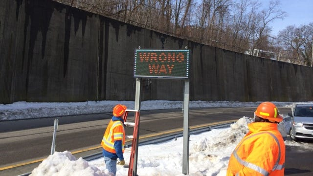 A work crew installs a Wrong Way sign at Exit 10 on the Thruway.
