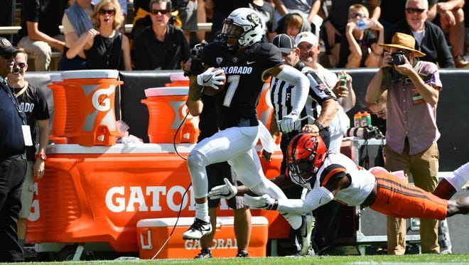 Colorado wide receiver Shay Fields (1) carries the ball for his third touchdown reception as Oregon State safety Brandon Arnold (3) attempts to tackle him in the first half at Folsom Field. Colorado won 47-6.