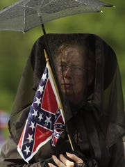 In this June 12, 2004 file photo, a mourner holds a Confederate flag as she waits in line to pay respects to Alberta Martin in Curtis, Ala. Martin, the last widow of a Civil War veteran, died May 31.