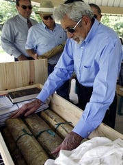 Art Wolff places a section of a Torah known locally