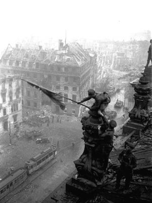 FILE- In this May 2, 1945 file photo, Soviet soldiers hoist the red flag over the Reichstag after the fall of Berlin, which became one of the iconic images of World War II taken by renowned photographer Yevgeni Khaldei.  The daughter of the photographer Yevgeni Khaldei who took the iconic WWII image of Red Army soldiers atop the Reichstag, Anna Khaldei has regained possession of his original negatives after a 15-year court battle and is now hoping to mount an exhibition of her father's work, recording history through his lens.