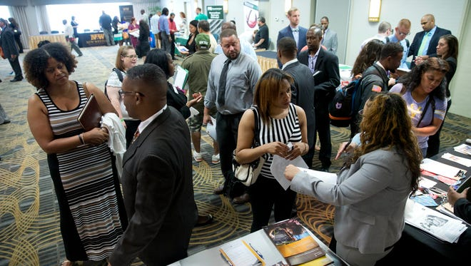 Job seekers and recruiters meet Monday during a job fair in Philadelphia.