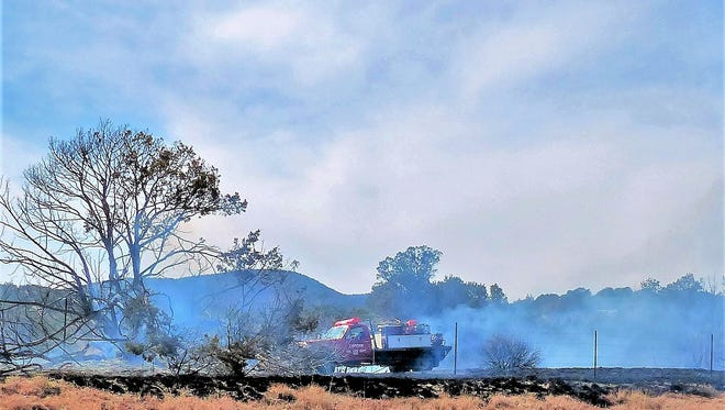 A brush unit works on a charred area west of Cemetery Road.