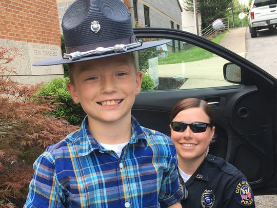 Uriah Moore tries on the hat of Erin Police Officer