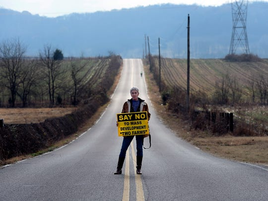 Anne Goetze stands in the middle of West Harpeth Road on Dec. 7, 2016, in Thompson's Station. The land to the left and right of Goetze is a proposed development of 2,000 acres.