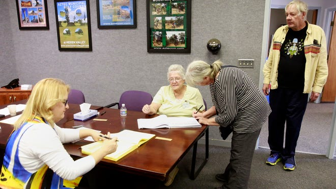 Election clerks Denise Bradford, left, and Frances Cooper, second from left, confirm the registration of Deb Fisher and Jim Fisher before handing them ballots and sending them to the voting machines on Tuesday at Aztec City Hall.
