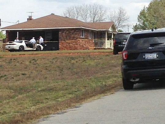 Vehicles block Cloverhill Drive near Anderson on March 27 as the coroner and detectives from the Anderson County Sheriff's Office investigate a fatal shooting at the house.