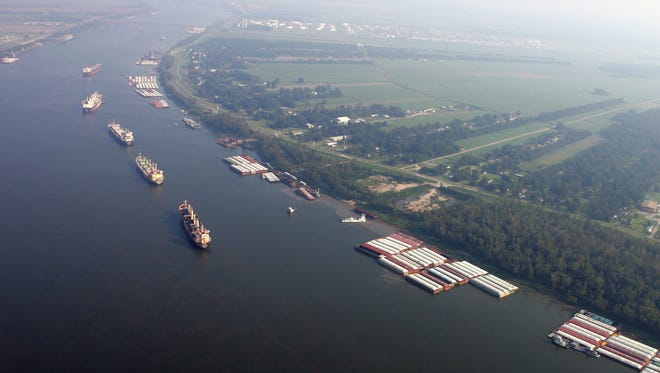 This 2005 file photo shows ships and cargo containers along the Mississippi River  in this aerial view, between Baton Rouge and New Orleans.  A few Louisiana businessmen and politicians are dreaming big, as big as the mega-ships of the future that may grow so large they won't be able to make into the Mississippi River and up to the Port of New Orleans. (AP Photo/David J. Phillip, Pool, File)