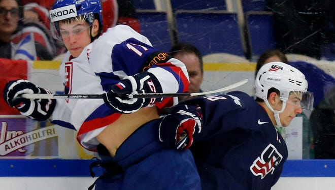 Slovakia's Eduard Simun, left, collides with the USA's Connor Carrick during the second period.