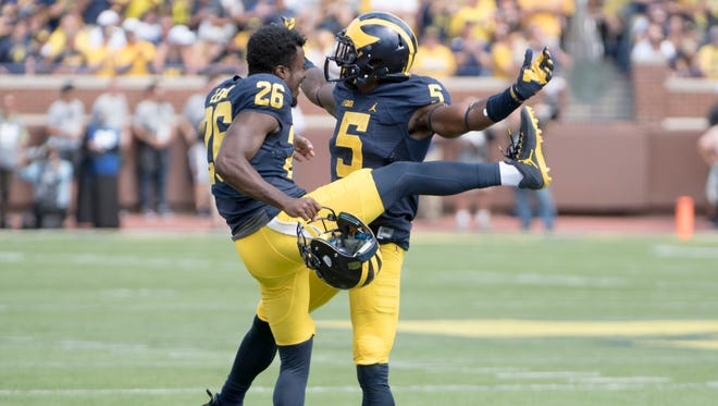Jourdan Lewis, left, helps Jabrill Peppers celebrate a return by Peppers in the first half Saturday.