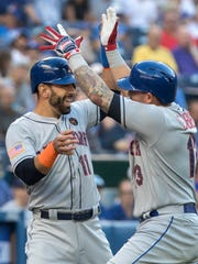 New York Mets' Asdrubal Cabrera, right, celebrates with teammate Jose Bautista after Cabrera hit a two-run home run against the Toronto Blue Jays during the first inning of a baseball game Tuesday, July 3, 2018, in Toronto.