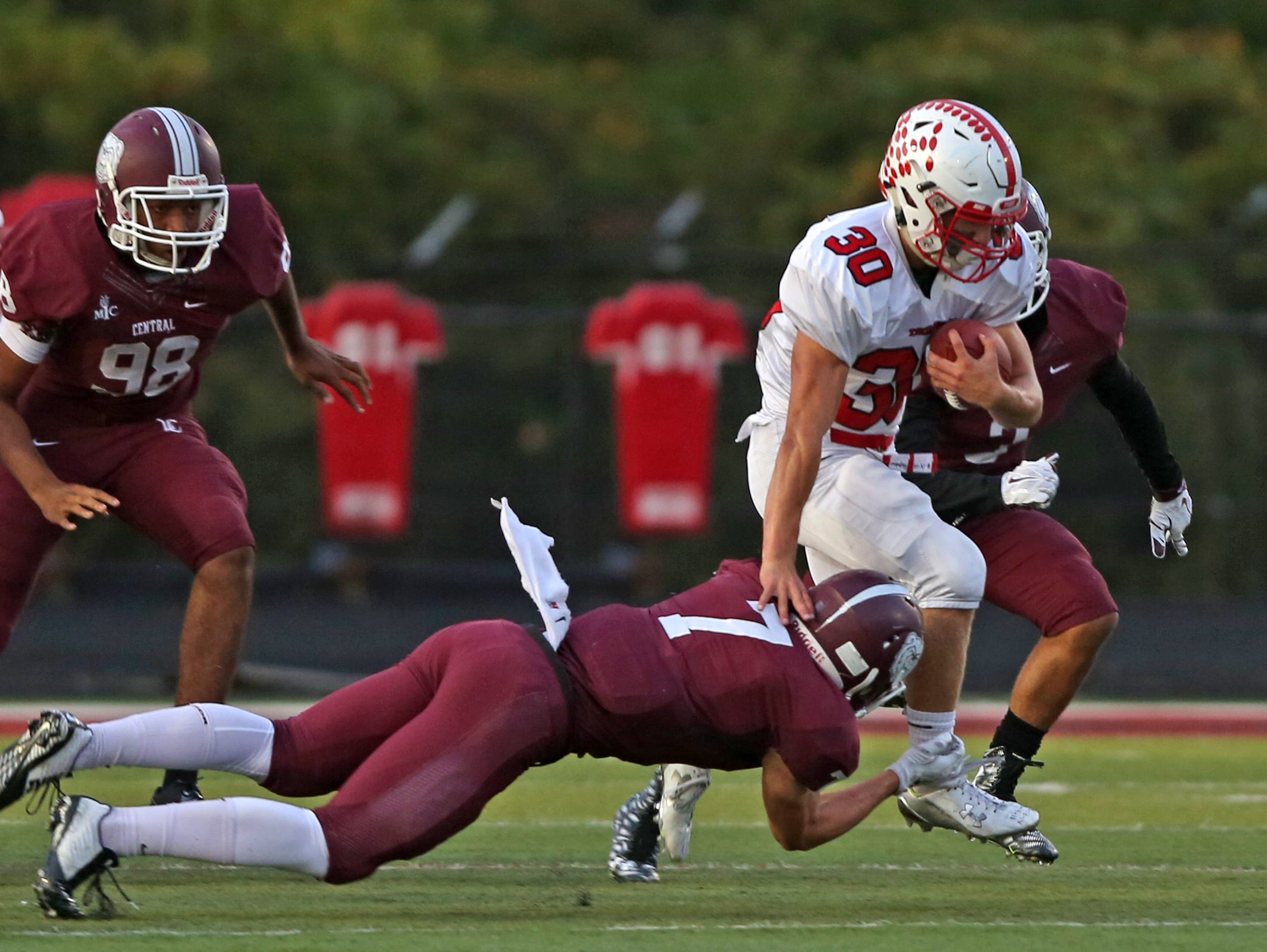 Center Grove Titus McCoy moves pass Lawrence Central defense including LC #7 Michael Tutsie in first half action during the Center Grove at Lawrence Central football game, Friday, September 25, 2015. Center Grove won 44-26.