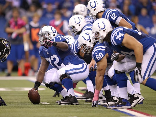 Colts center Jonotthan Harrison (72) points out the