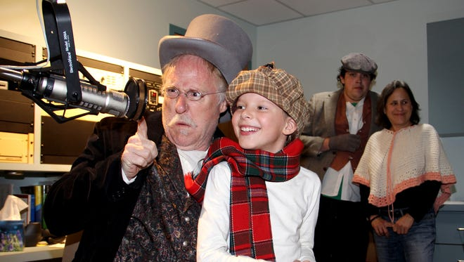 """Charles Pike, left, and Devyn Erikson are pictured during KSJE's on-air performance of """"A Christmas Carol"""" last year."""