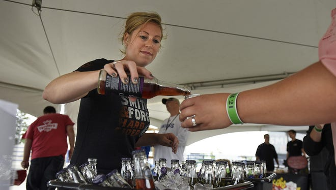 Cassey Schmidt of Crispin Cider Company pours samples during Ciderfest on Saturday at Joe Faber Field.
