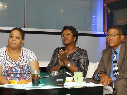 Leslie Rowans,  National Coalition of 100 Black Women Phoenix Metro Chapter President Charlene Tarver  and Lincoln Ragsdale Jr. watch the presidential debate during a party organized by the group  on  Oct. 19, 2016, in Phoenix.