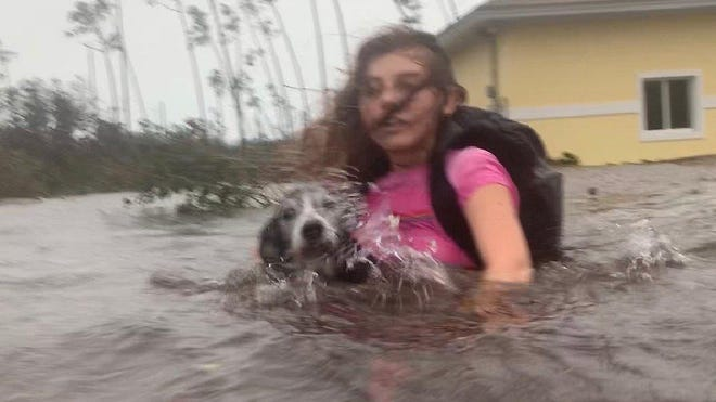 Julia Aylen wades through waist deep water carrying her pet dog as she is rescued from her flooded home during Hurricane Dorian in Freeport, Bahamas, on Tuesday.