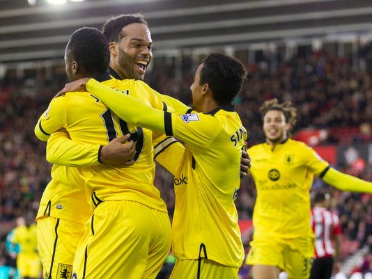 Aston Villa's Joleon Lescott, center, celebrates scoring his side's first goal of the game with teammates Jordan Ayew, left, and Scott Sinclair during their English Premier League soccer match against Southampton at St Mary's Stadium, Southampton, England, Saturday, Dec. 5, 2015. (Chris Ison/PA via AP)     UNITED KINGDOM OUT     -   NO SALES     -    NO ARCHIVES