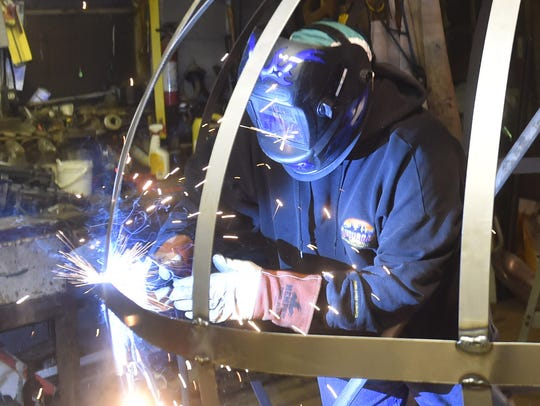 Engineer Corey Corbisier works on the frame of the
