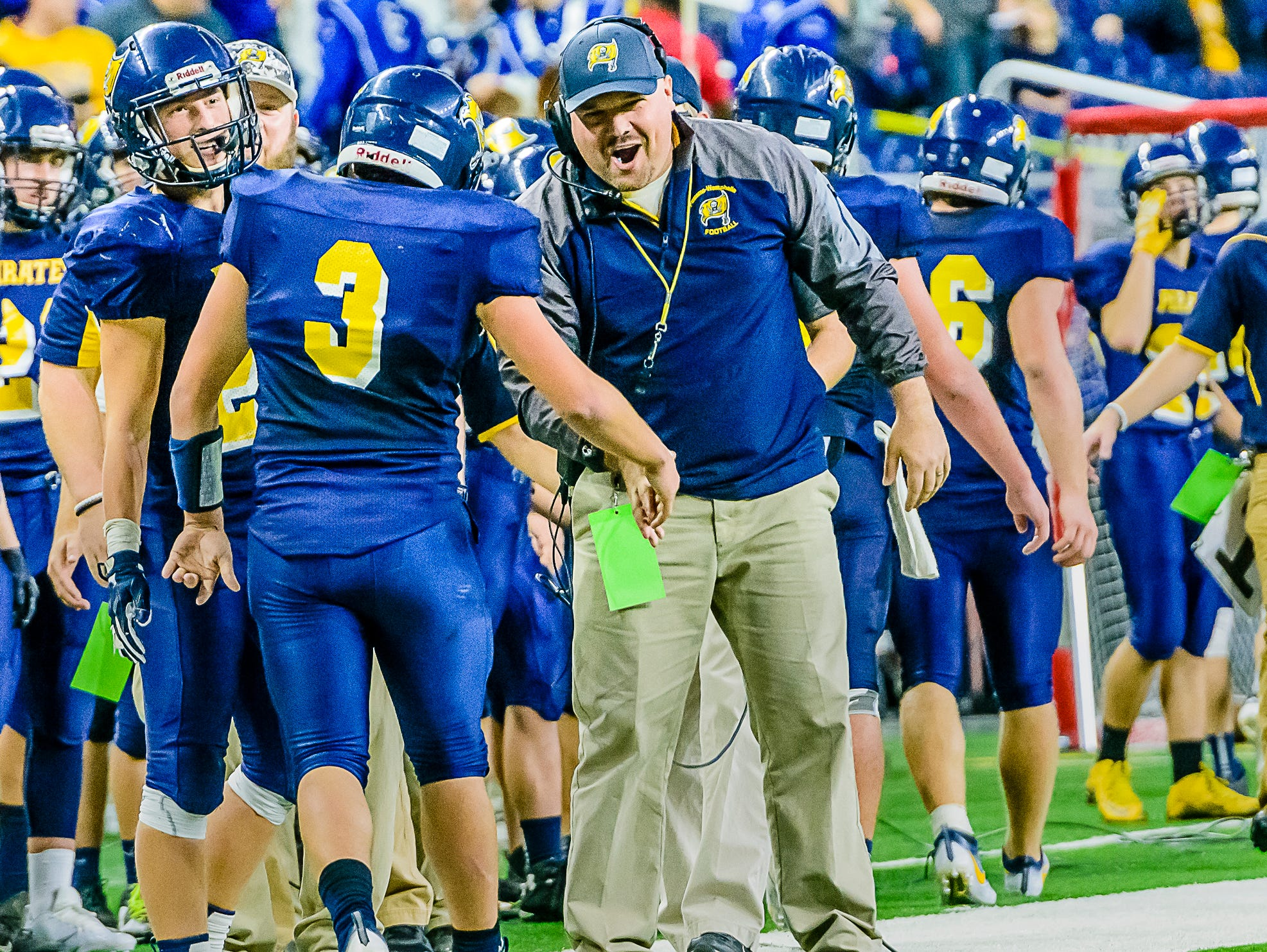 Pewamo-Westphalia Head Football Coach Jeremy Miller ,right, congratulates quarterback Ryan Smith after he scored on a keeper around the right end to put the Pirates up 20-0 with 34 seconds remaining in the 3rd quarter.