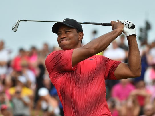 Tiger Woods plays his shot from the 18th tee during