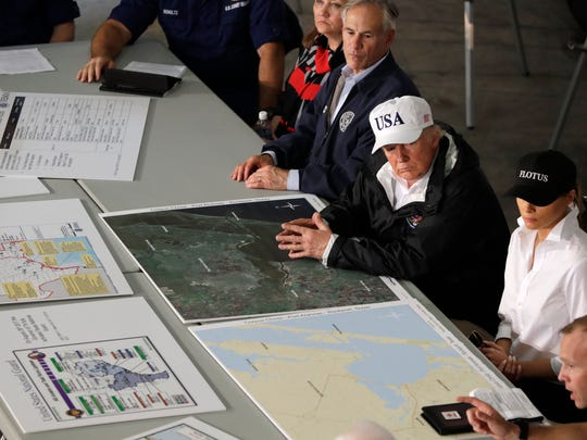 President Donald Trump, flanked by Texas Gov. Greg Abbott and first lady Melania Trump listens during a briefing on Harvey relief efforts, Tuesday, August 29, 2017, at a fire station in Corpus Christi, Texas. (AP Photo/Evan Vucci)