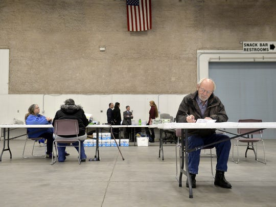 A few voters fill out their ballots at the polling center in Exhibition Hall on Tuesday afternoon.