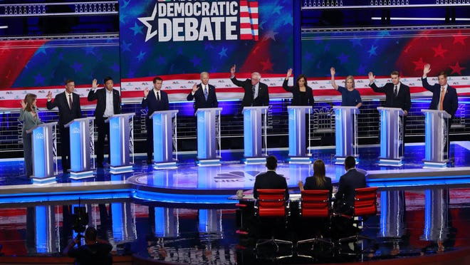 Democratic presidential candidates, author Marianne Williamson, former Colorado Gov. John Hickenlooper, entrepreneur Andrew Yang, South Bend Mayor Pete Buttigieg, former Vice President Joe Biden, Sen. Bernie Sanders, I-Vt., Sen. Kamala Harris, D-Calif., Sen. Kirsten Gillibrand, D-N.Y., former Colorado Sen. Michael Bennet, and Rep. Eric Swalwell, D-Calif., raise their hands when asked if they would provide healthcare for undocumented immigrants, during the Democratic primary debate hosted by NBC News at the Adrienne Arsht Center for the Performing Arts, Thursday, June 27, 2019, in Miami.