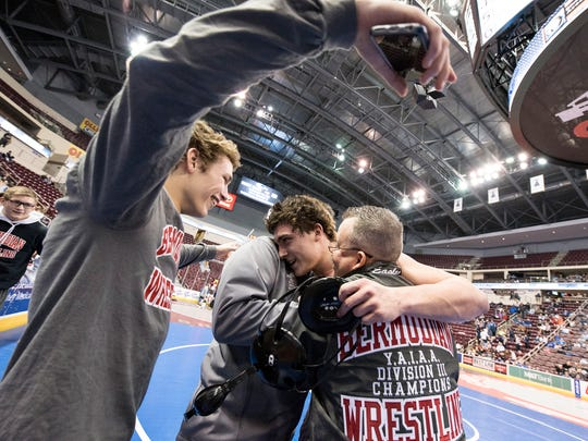 Bermudian Springs' Chase Dull embraces his coaches after winning his 195-pound championship over Newport's Brady Herr, 5-2, at Hershey's Giant Center for the District 3 tournament, Saturday, Feb. 24, 2018.