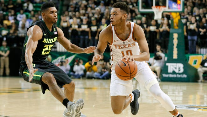 Baylor's Al Freeman (25) defends as Texas's Eric Davis Jr. (10) drives to the hoop during Tuesday's game.