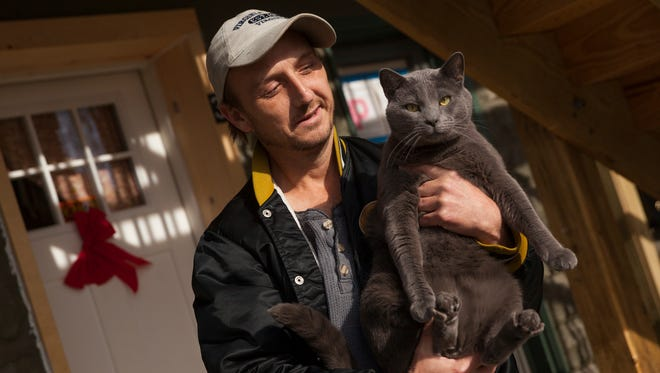 Scott Lucas, who has lived at 240 Kalorama Street for over 20 years, poses with one of his cats, Smokey, outside his recently renovated apartment unit on Friday, Dec. 26, 2014. The affordable housing non-profit Valley Area Community Support has been fixing up the building and preparing new units for incoming tenants.