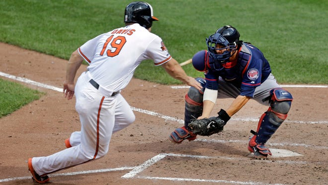 The Orioles' Chris Davis but can't beat Minnesota Twins catcher Kurt Suzuki's tag at home plate in the seventh inning Monday in Baltimore. Minnesota won 6-4.